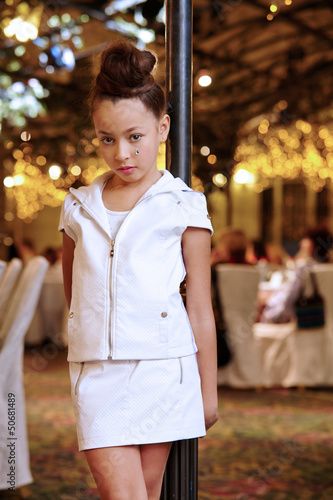 Girl in white leather suit stands near decorative lamppost