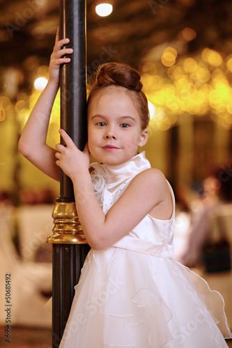 Little girl in white evening dress stands