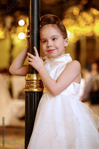 Little girl in white evening dress stands smiling slightly