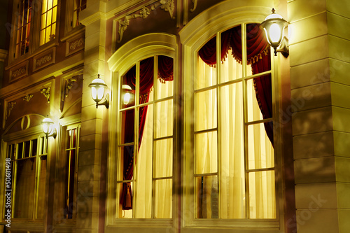 Arched windows on facade of house, lit by lanterns in evening
