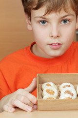 Boy in orange t-shirt holds open box of corrugated cardboard