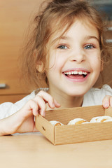 Smiling girl holds open box of corrugated cardboard with cake