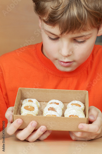 Boy  look at open box of corrugated cardboard with cake