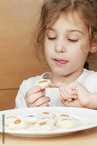 Gir, licking her lips, sits at plate of cookies with almonds