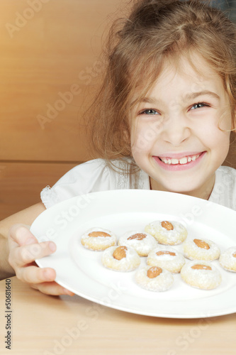 Smiling little girl holds plate with cookies with almonds