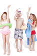 Three children in beach suits with beach accessories