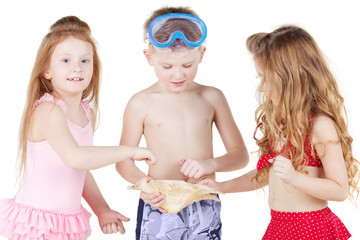 Boy and two girls in beach suits, boy holds big seashell