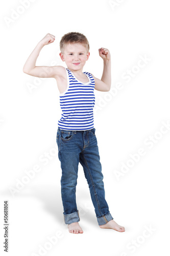 Smiling boy strains biceps and shows how strong he is