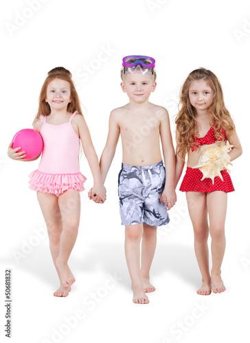 Three children in beach suits go holding hands