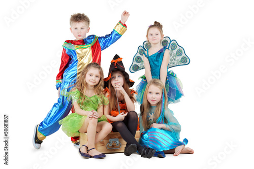 Children in carnival costumes sit on chest and stand beside