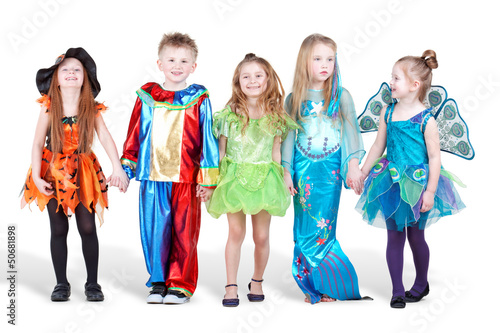 Smiling children dressed in carnival suits stand holding hands