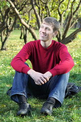 Young man in red sweater smiles and sits on grass in park