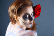 Melancholy zombie girl with painted face and two red roses