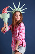 Pretty girl in pink shirt with crown and torch represents statue
