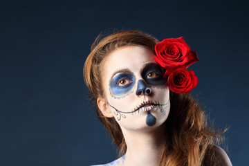 Pretty zombie girl with painted face and two red roses in hair