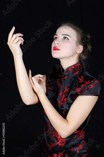 Young girl in Japanese silk blouse dances and looks up at black