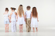 Back of four cute little girls and one boy in white clothes