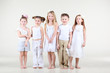 Four cute little girls and one boy in white clothes stand