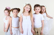 Five cute little children in white clothes stand and look