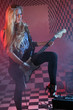 Beautiful girl holds electric guitar in studio in smoke