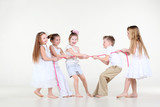 Five happy little children in white clothes draw over pink rope.