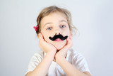 Little melancholy girl in white with glued fake black mustache. poster