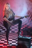 Beautiful blonde girl holds electric guitar in studio in smoke