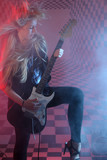 Beautiful blonde girl with flowing hair holds electric guitar