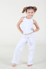 Little smiling girl in clean white clothes stands and poses.