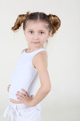 Little serious girl in white shirt and pants stands