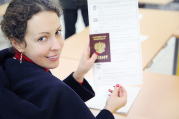 Woman shows passport and voting paper at elections
