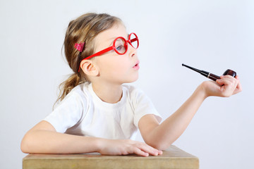 Little girl in big glasses sits at table and holds pipeful.