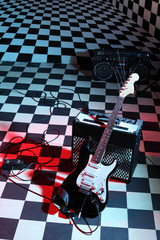 Guitar and sound amplifying equipment in studio on checkerboard