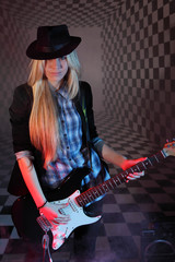 Beautiful blonde girl in hat with guitar in studio in smoke.