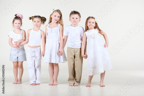 Four cute little girls and one boy in white clothes stands