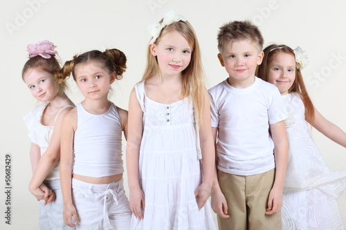 Five smiling children in white clothes stand and look at camera.
