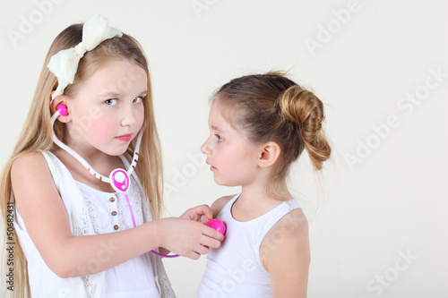 Little girl in white dress listens heartbeat of another girl