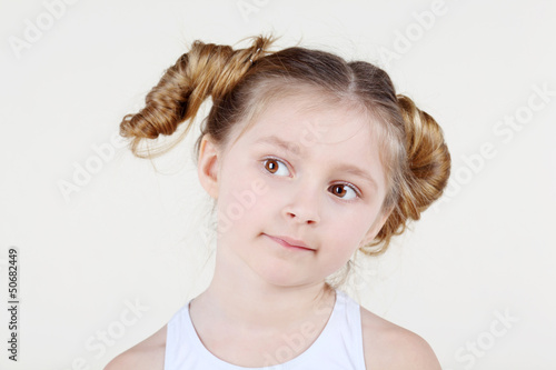 Little thoughtful girl with funny hairdo in white shirt