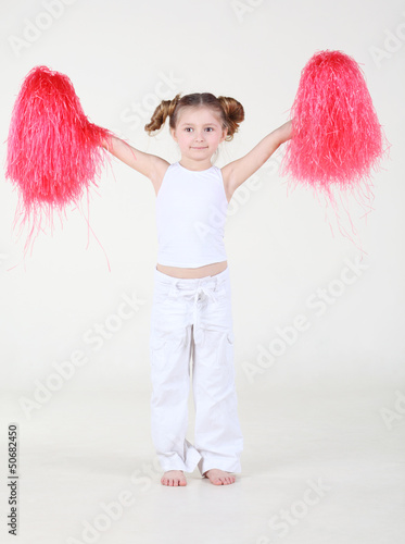 Little happy girl with funny hairdo holds pompons