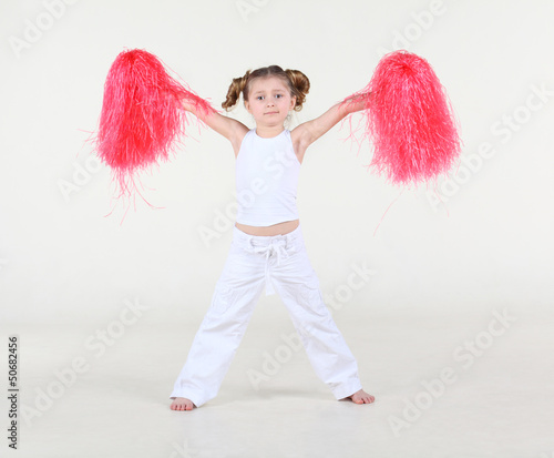 Little barefoot girl with funny hairdo holds pompon