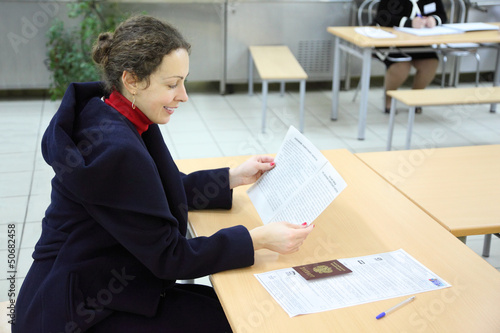 Woman reads documents in elections to State Duma
