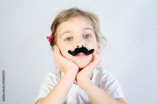 Little melancholy girl in white with glued fake black mustache.
