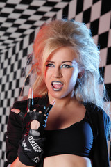 Young woman rocker in biker gloves screams in studio
