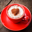 Red cup with cappuccino and heart decoration over foam.