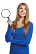 Smiling young female holding magnifying glass