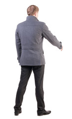 back view of businessman in coat reaches out to shake hands.