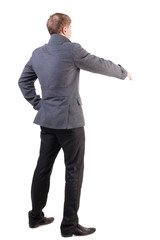 back view of businessman in coat reaches out to shake hands