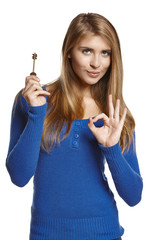 Young woman holding key and making OK gesture