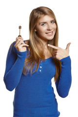 Young woman holding key and pointing at it