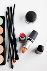 Makeup brushes and cosmetics on a white background